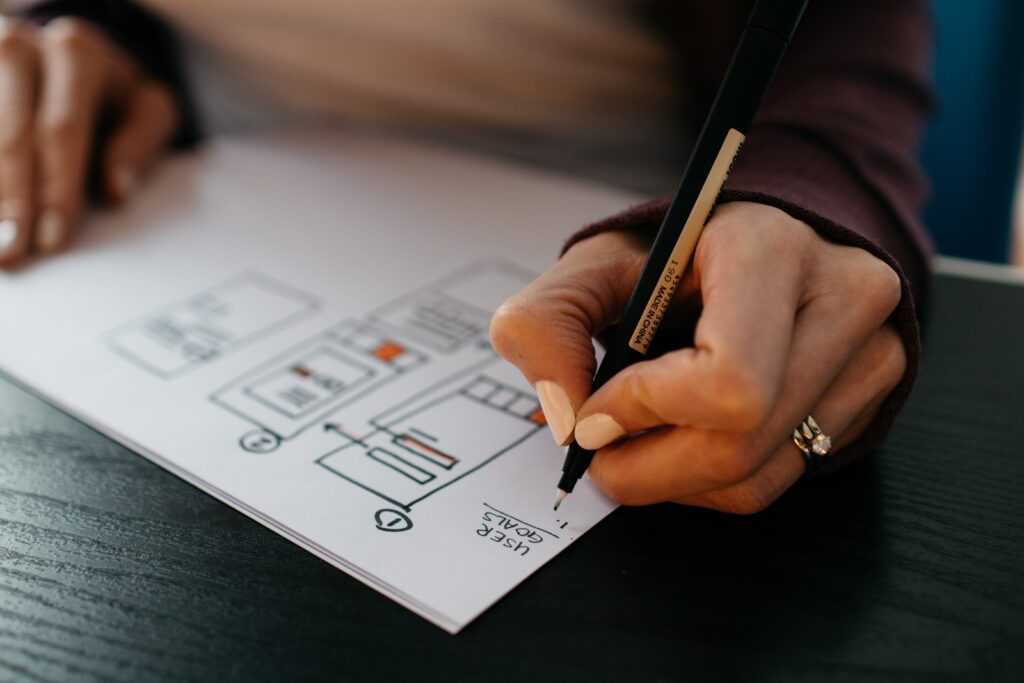 A woman drawing wireframes of a mobile app