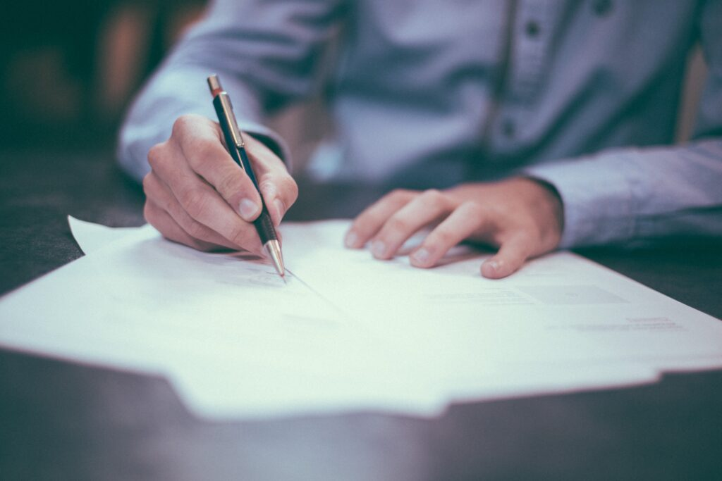 Person holding a pen completing paperwork