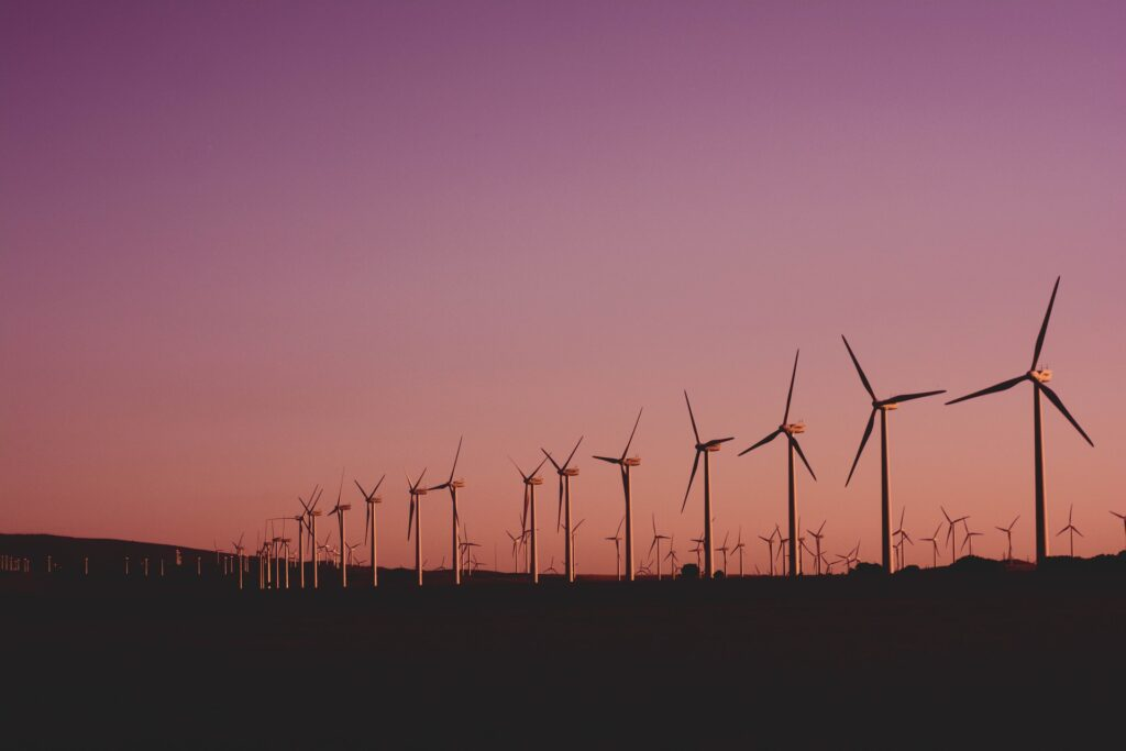 A row of wind turbines during a sunset