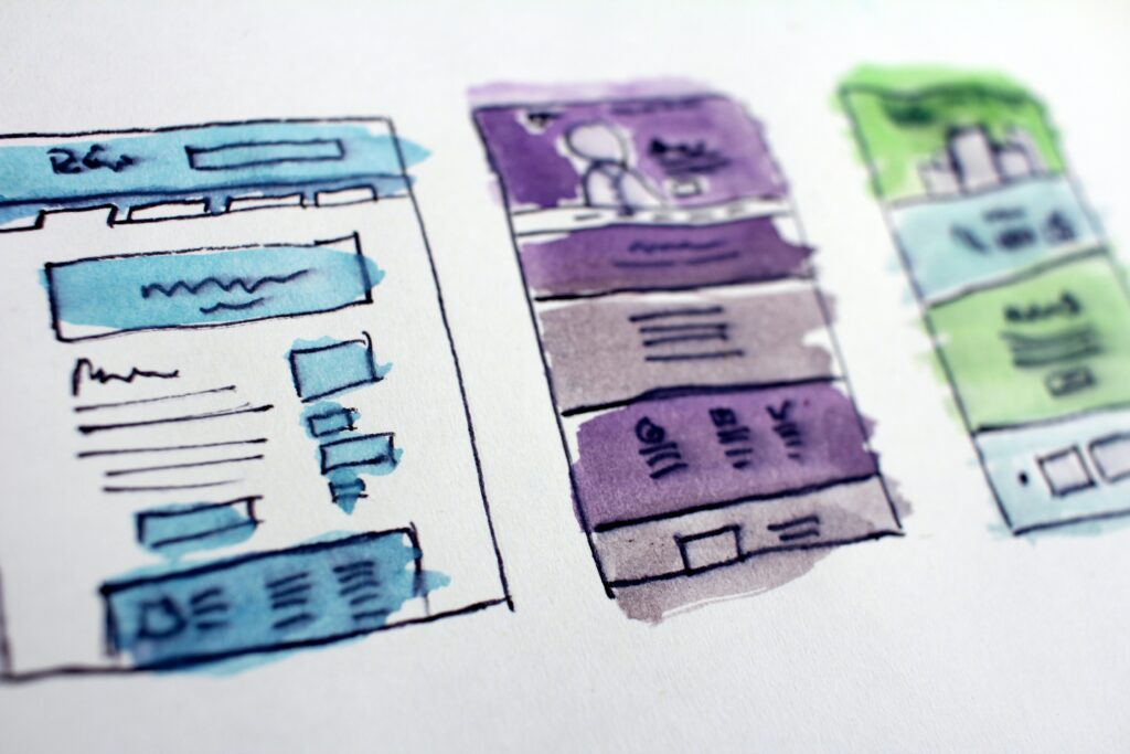 Wireframe of an app. Each screen from left to right is coloured in blue, purple and green.